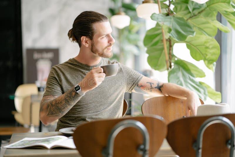 Tiempo del caf? Retrato del hombre barbudo del inconformista hermoso que goza de una taza de caf? que se relaja y que mira lejos  imagen de archivo