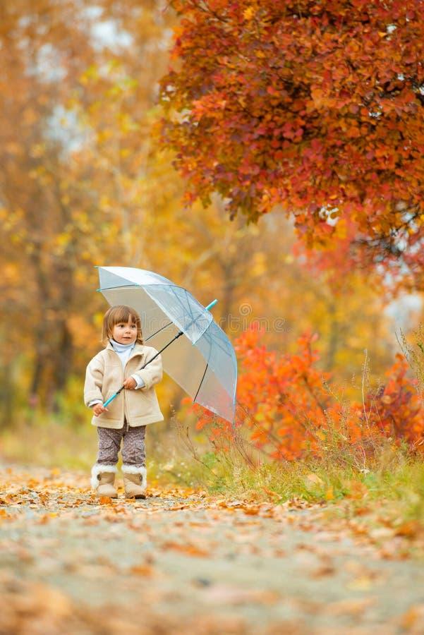Tiempo del otoño, la niña feliz está caminando a lo largo de la trayectoria con un paraguas en la caída en la naturaleza, caminan foto de archivo