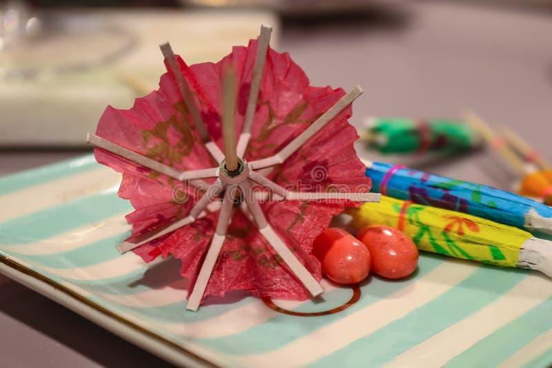Tiempo del partido - paraguas de papel borrosos del cóctel en una bandeja con las habas de una jalea de los pares - primer - foco imagen de archivo