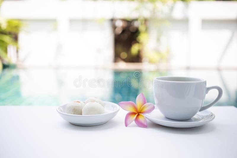Tiempo del té de tarde en el lado de la piscina, taza de té blanca con el dulce tailandés en la tabla blanca sobre fondo borroso  foto de archivo