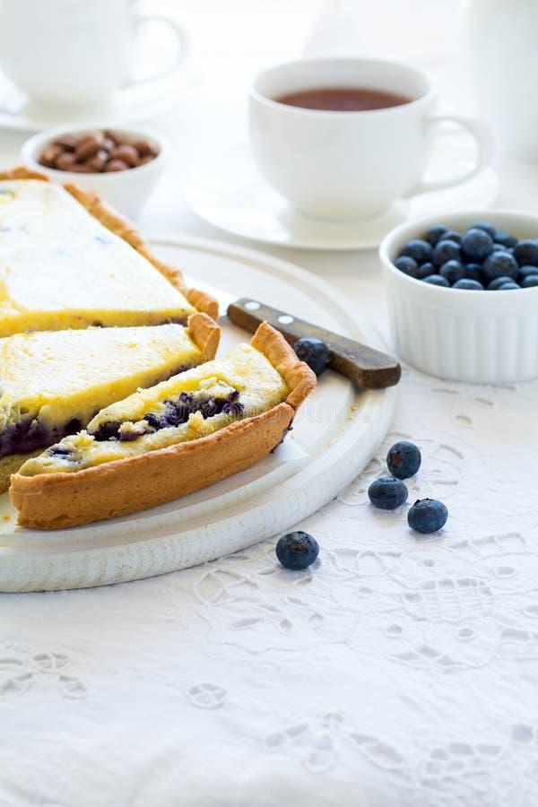 Tiempo del té Pastel de queso hecho en casa del arándano, tazas de té, nueces y baya imagenes de archivo