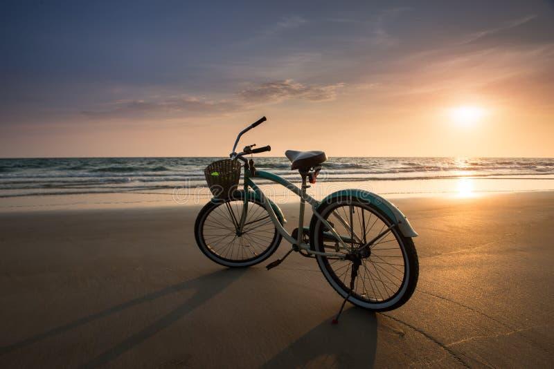 Tiempo determinado de Sun con la bicicleta en la playa imagen de archivo
