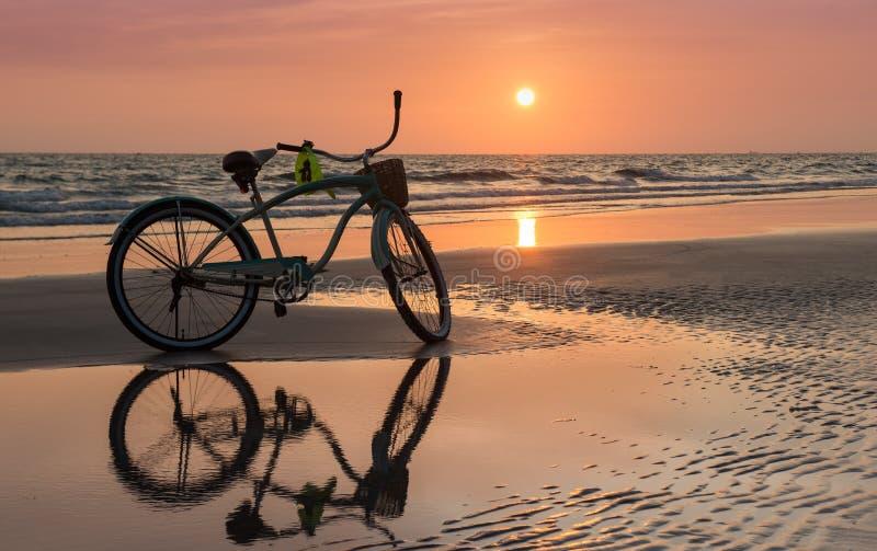 Tiempo determinado de Sun con la bicicleta en la playa fotografía de archivo