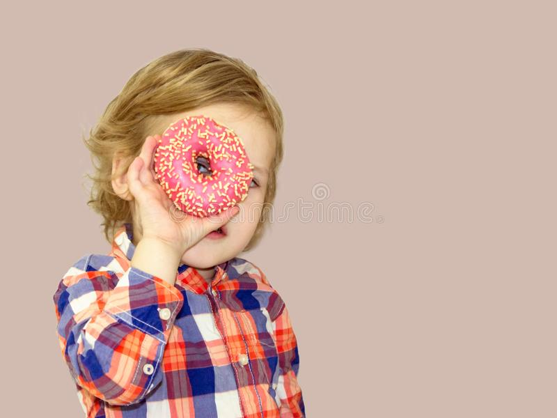 Tiempo divertido con la comida dulce Bebé brillante en una camisa de tela escocesa imagenes de archivo