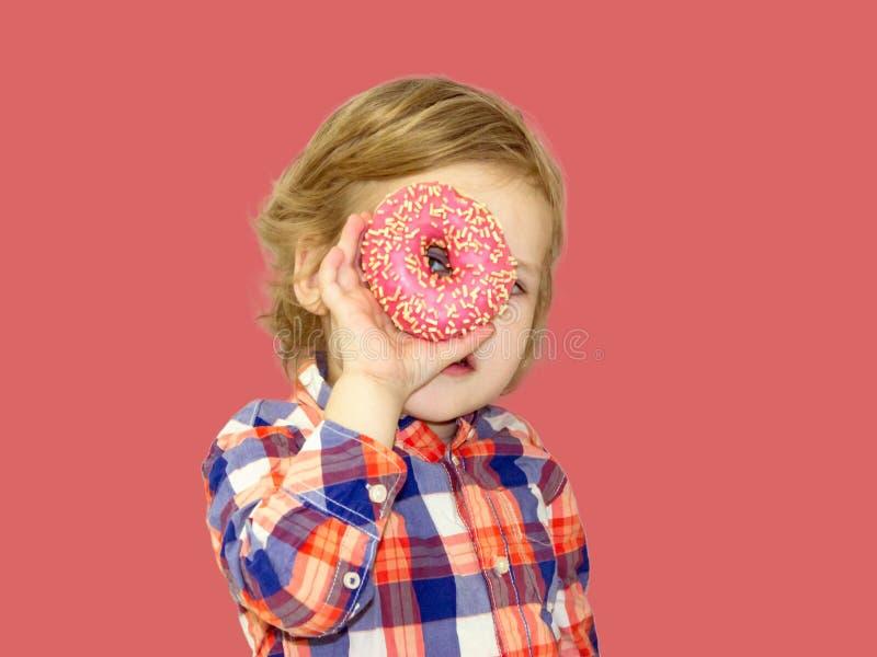 Tiempo divertido con la comida dulce Bebé brillante en una camisa de tela escocesa fotografía de archivo libre de regalías