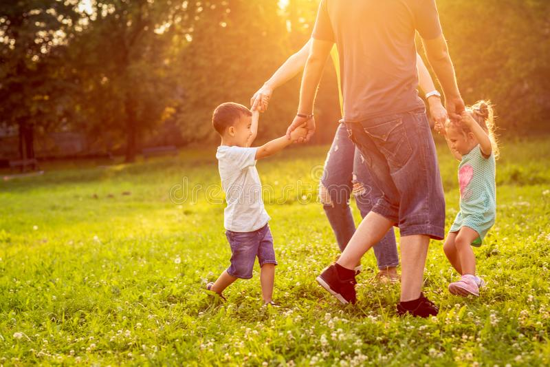 Tiempo divertido - familia feliz que juega al juego con sus ni?os en la hierba en el parque imágenes de archivo libres de regalías