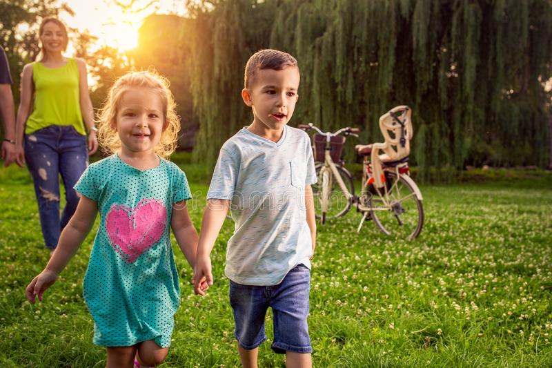 Tiempo divertido - ni?os jovenes hermosos que caminan con los padres en parque imagen de archivo libre de regalías