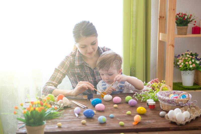 Tiempo feliz mientras que pinta los huevos de Pascua Concepto de Pascua Madre feliz y su niño lindo que consiguen listos para Pas fotografía de archivo libre de regalías