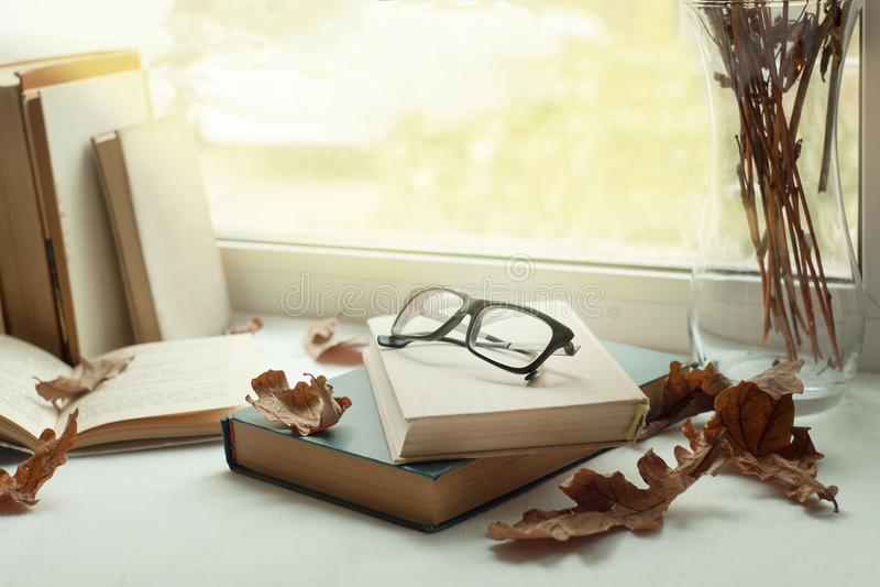 Tiempo libre, lectura y reclinación ventana con las hojas de otoño, un libro, vidrios, hora de leer, concepto del fin de semana d fotografía de archivo