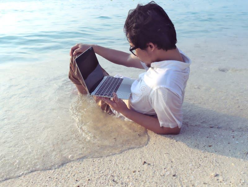 Tiempo relajado y de verano del hombre asiático en ropa casual con el ordenador portátil que se acuesta en la playa tropical con  foto de archivo libre de regalías