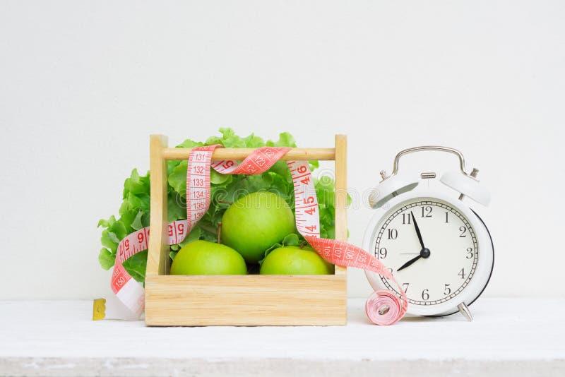 Tiempo sano y concepto de dieta Despertador retro del vintage y manzanas y lechuga verdes en la cesta de madera en de madera blan fotografía de archivo libre de regalías