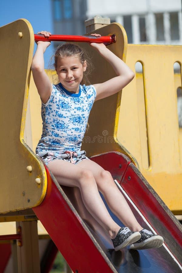 Tien jaar oud meisjes heeft pret op kinderenspeelplaats terwijl het zitten op glijdende raad stock fotografie
