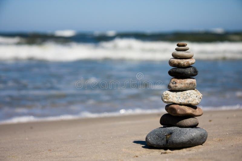 Tien kiezelstenen die op strand worden gestapeld stock foto's