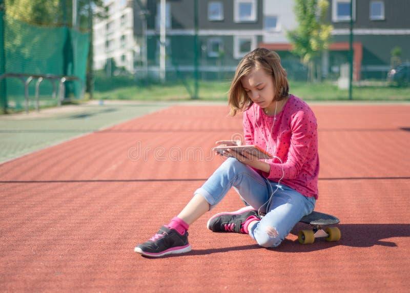 Tien meisje met koptelefoon en tablet stock fotografie