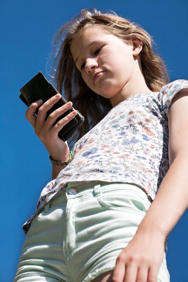 Tien meisje met mobiele close-up bottom-up visie van de telefoon stock foto's