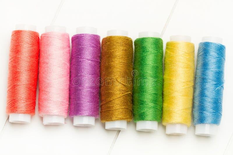 Tien spoelen van gekleurde draden stock foto