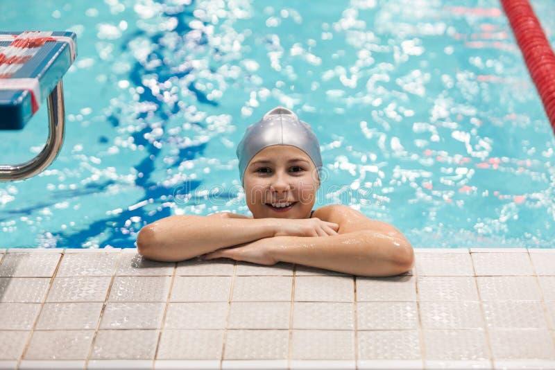 Tien van de meisjesjaar zwemmer die zich in zwembad, het bekijken camera en het glimlachen bevindt stock foto