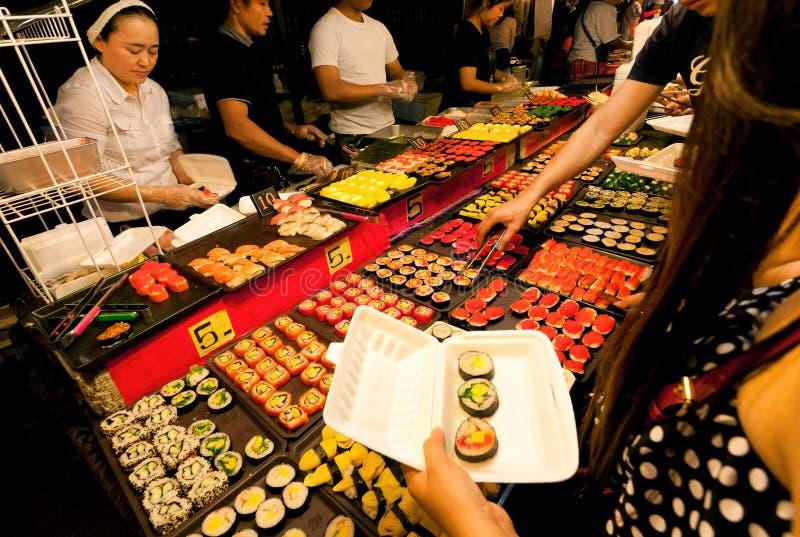 Tienda al aire libre del sushi que vende las delicadezas de los mariscos durante mercado de la noche con la zona de restaurantes  fotografía de archivo libre de regalías