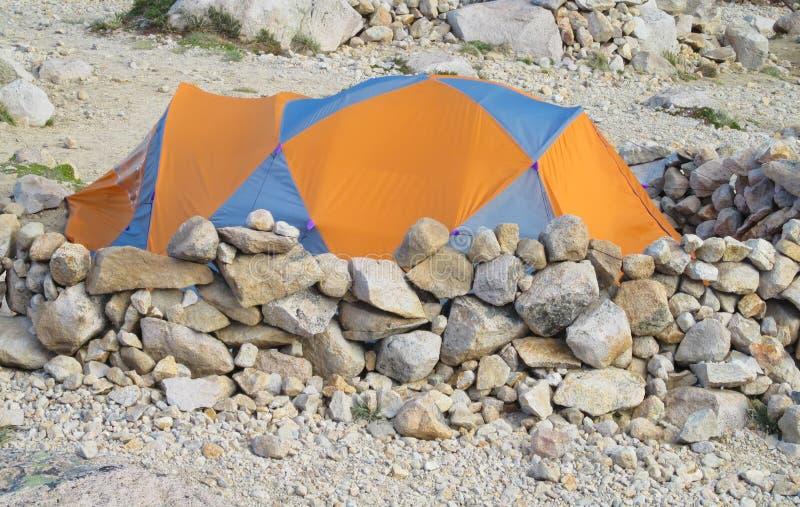 Tienda anaranjada en las rocas en las montañas imágenes de archivo libres de regalías