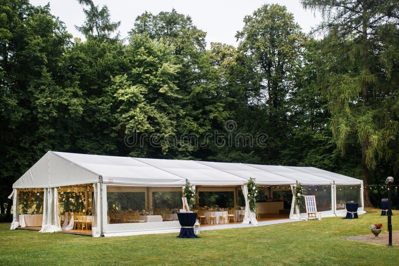 Tienda blanca larga para el banquete de boda en el bosque imagen de archivo