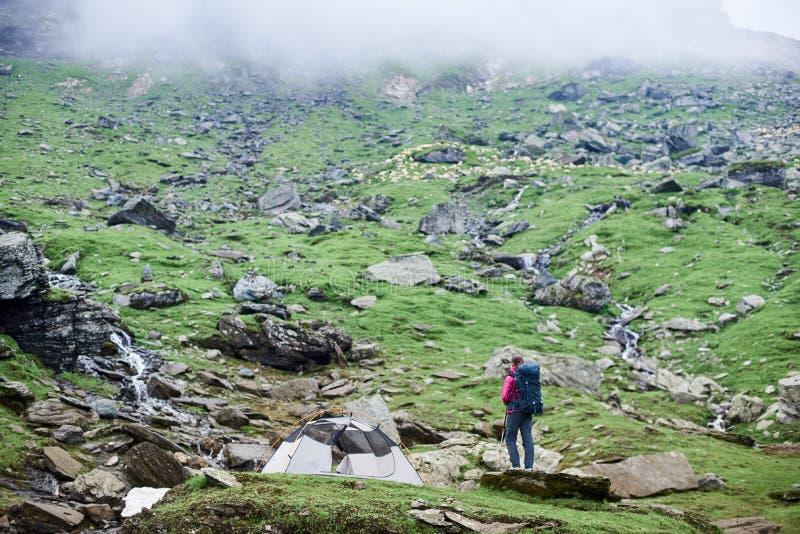 Tienda cercana turística femenina en la cuesta rocosa de las montañas de Fagaras imagen de archivo libre de regalías