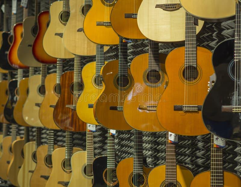 Tienda clásica de la música de fondo de la guitarra acústica con muchos guitarra imagen de archivo