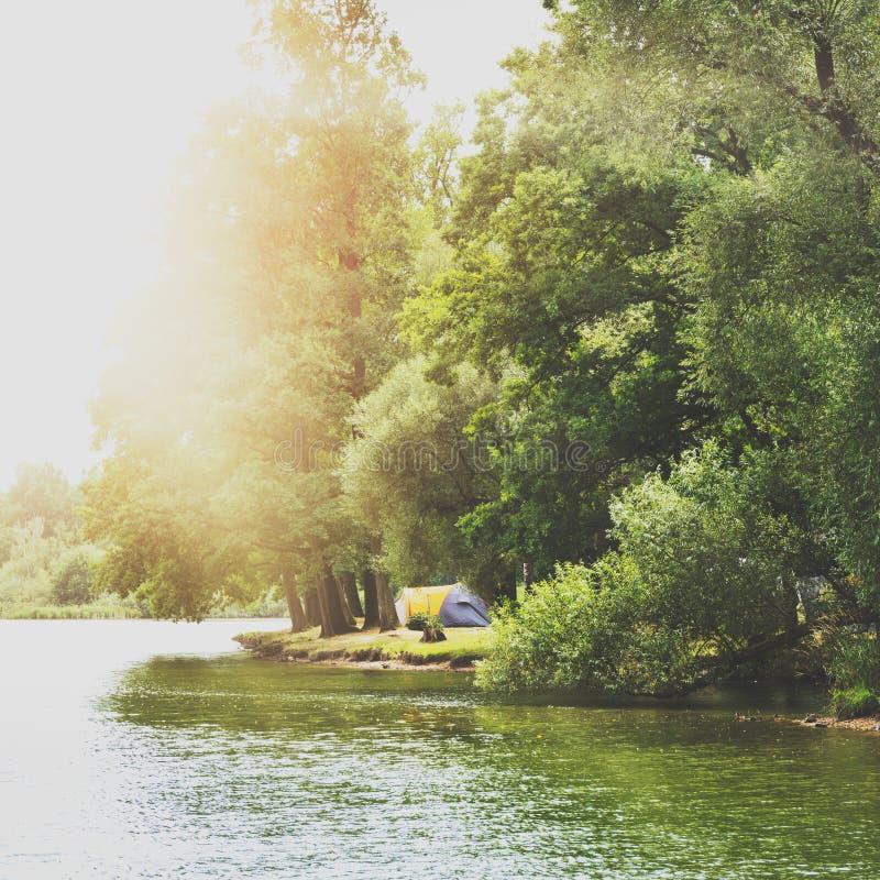 Tienda de campaña cerca de un lago hermoso, sitio para acampar del verano, concepto de las vacaciones de familia fotografía de archivo