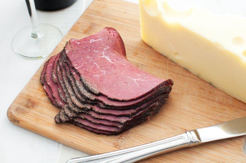 Tienda de delicatessen carne y queso en la tarjeta de corte foto de archivo