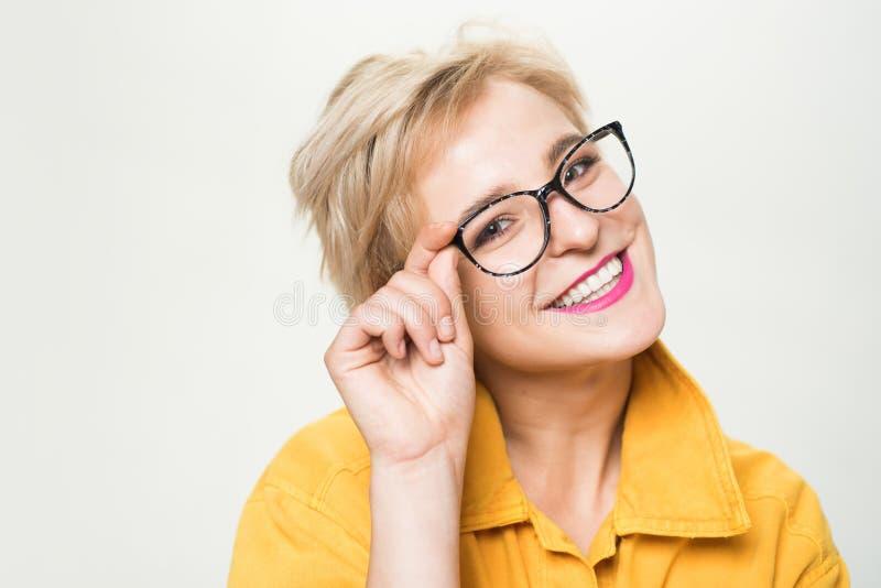 Tienda de la ?ptica Lentes de moda Lentes rubias sonrientes del desgaste de la mujer cerca para arriba Moda de las gafas Añada el fotos de archivo libres de regalías