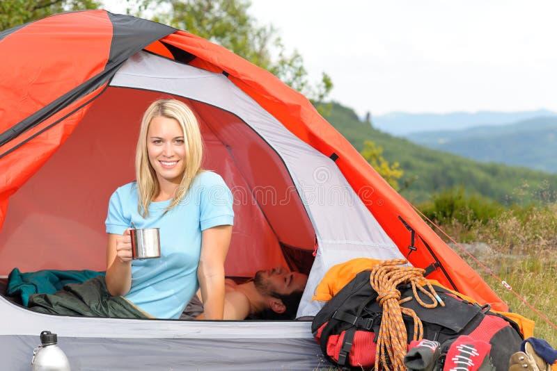 Tienda de la puesta del sol de la taza de la bebida de la mujer joven que acampa fotos de archivo