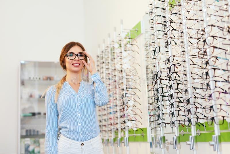 Tienda de las lentes Mujer que elige los vidrios para la corrección de la vista fotos de archivo