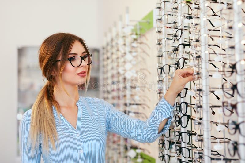 Tienda de las lentes Mujer que elige los vidrios para la corrección de la vista imagen de archivo libre de regalías