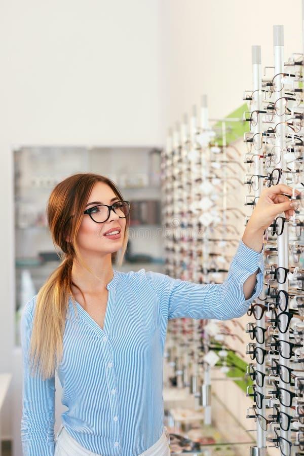 Tienda de las lentes Mujer que elige los vidrios para la corrección de la vista imagenes de archivo