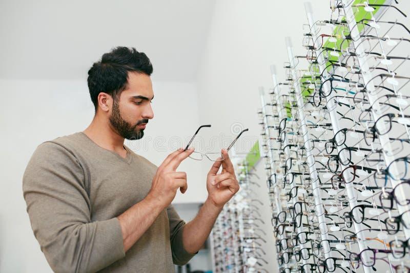 Tienda de los vidrios Hombre que intenta en las lentes en tienda de la óptica imagenes de archivo