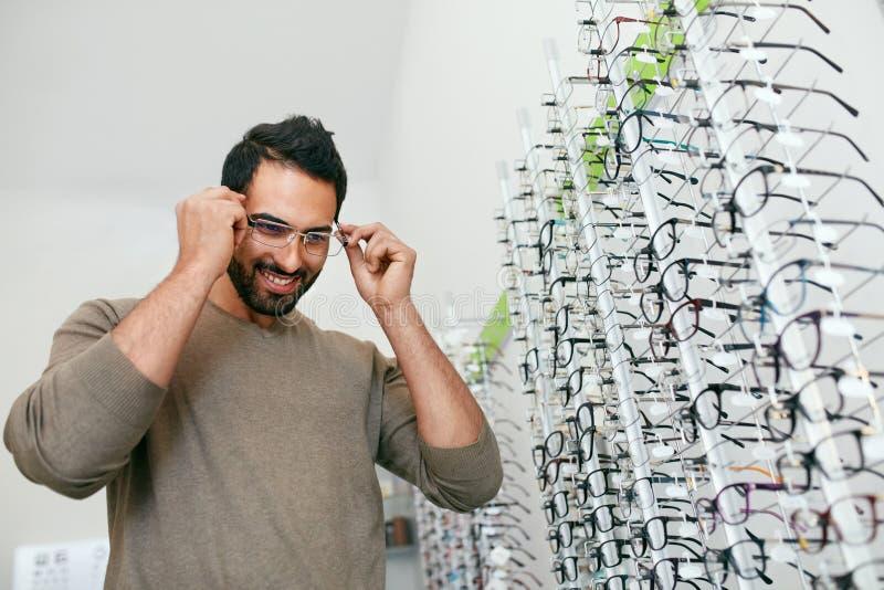 Tienda de los vidrios Hombre que intenta en las lentes en tienda de la óptica fotografía de archivo libre de regalías