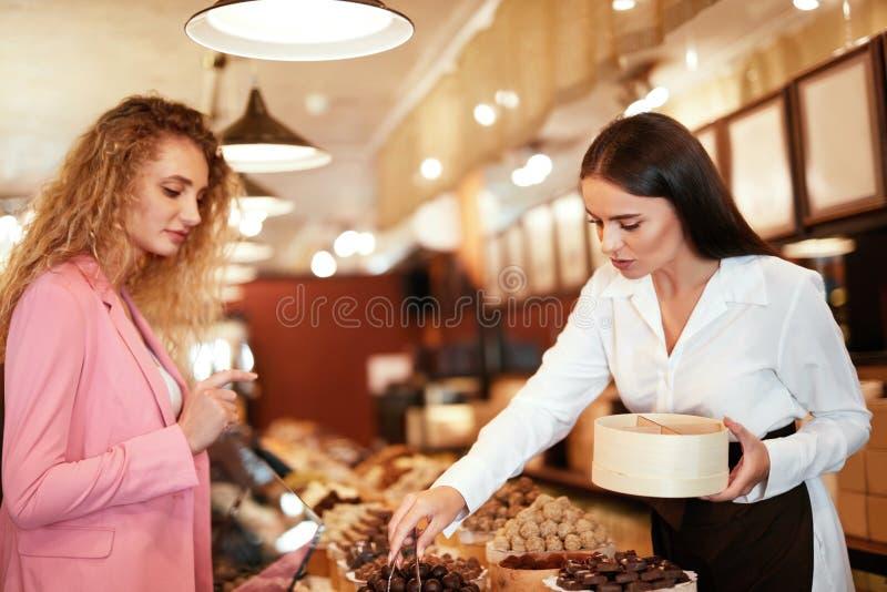 Tienda del chocolate Dulces de compra del chocolate de la mujer en tienda imagenes de archivo