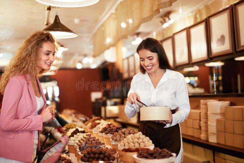 Tienda del chocolate Dulces de compra del chocolate de la mujer en tienda foto de archivo