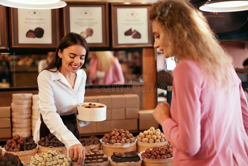 Tienda del chocolate Dulces de compra del chocolate de la mujer en tienda imagen de archivo libre de regalías
