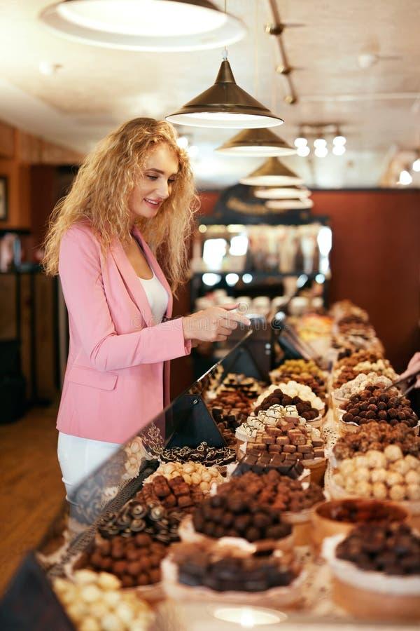 Tienda del chocolate Dulces de compra del chocolate de la mujer en tienda fotos de archivo