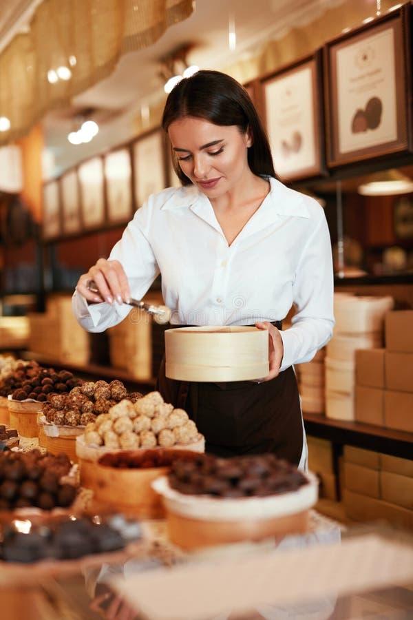 Tienda del chocolate Mujer que trabaja en tienda del chocolate fotos de archivo libres de regalías