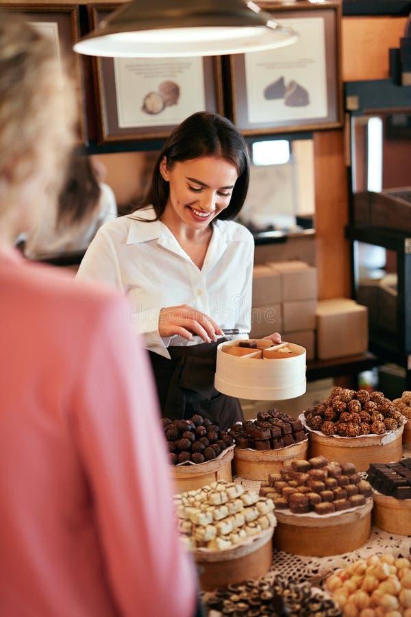 Tienda del chocolate Mujer que vende los dulces y los caramelos del chocolate fotografía de archivo