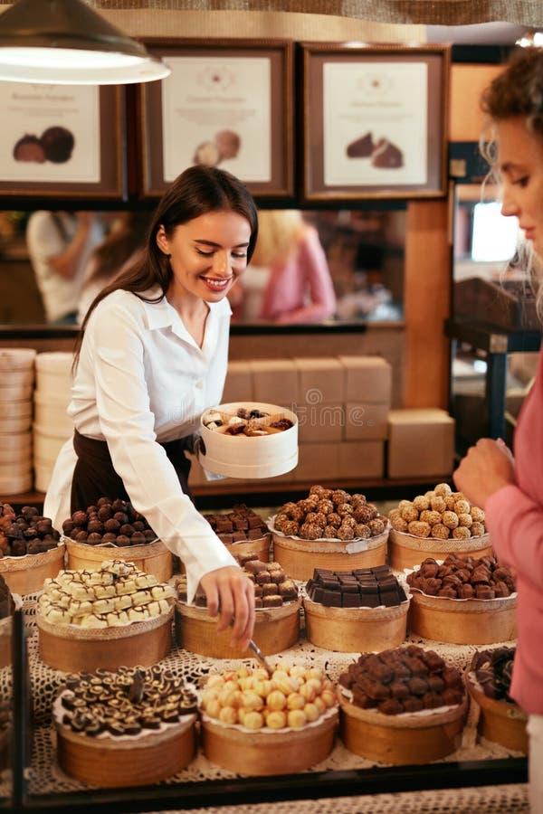 Tienda del chocolate Mujer que vende los dulces y los caramelos del chocolate foto de archivo libre de regalías