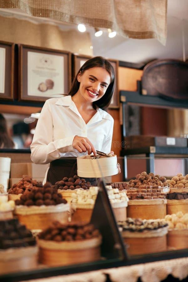 Tienda del chocolate Vendedor de sexo femenino en tienda de la confitería foto de archivo