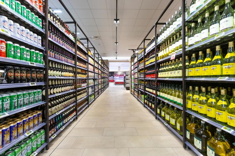 Tienda del vino y de la cerveza con una exhibición ancha de botellas de productos del departamento del vino fotos de archivo libres de regalías
