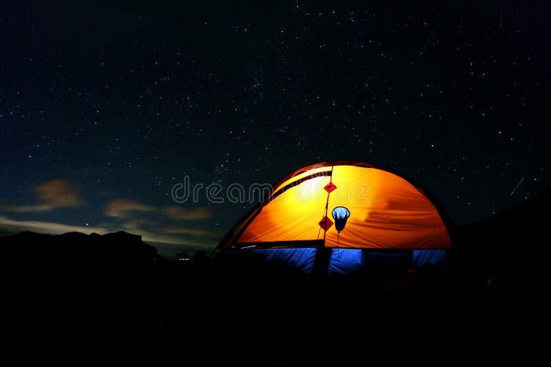 Tienda iluminada debajo del cielo nocturno estrellado imagenes de archivo