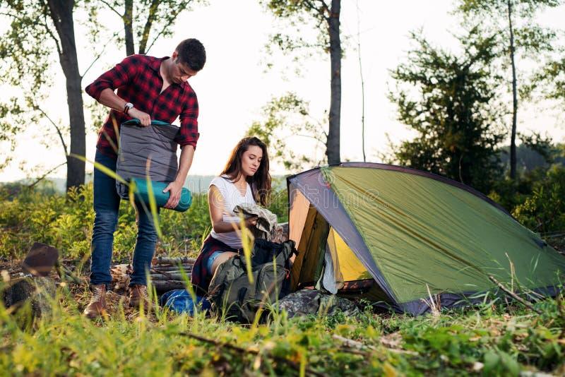 Tienda joven de la creación de los pares al aire libre, el caminar y el acampar imagen de archivo