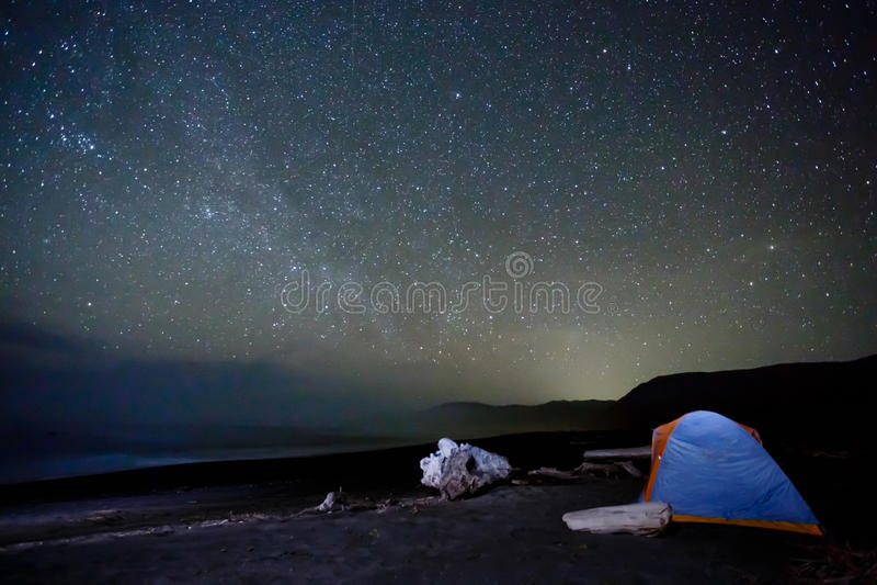 Tienda que acampa bajo miríada de estrellas brillantes en la playa fotos de archivo