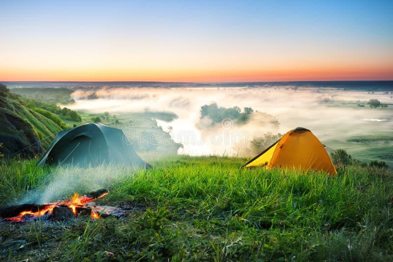 Tienda que acampa en la colina sobre el río brumoso imagenes de archivo