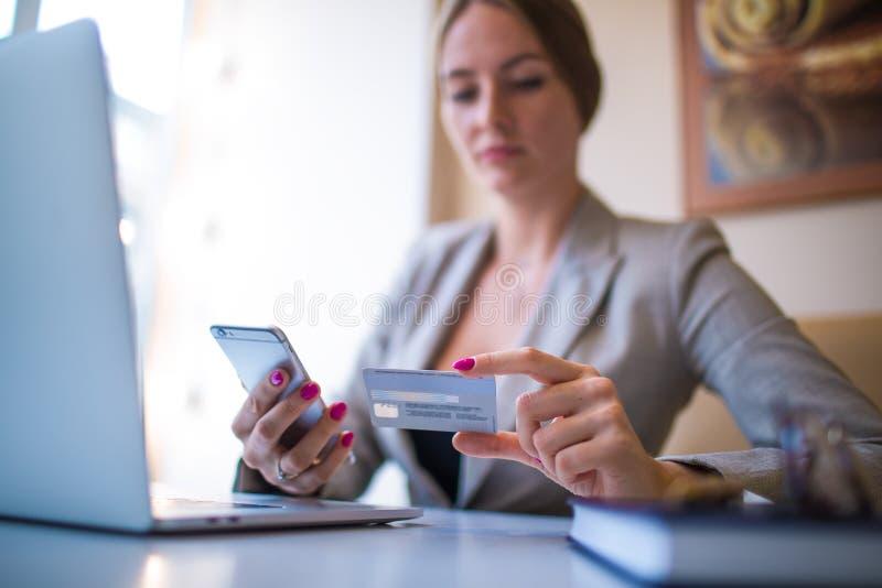 Tienda que hace compras en línea de fabricación femenina vía el artilugio del teléfono móvil foto de archivo