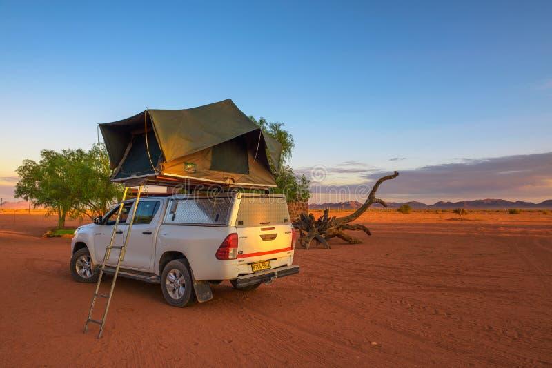 Tienda situada en el tejado de un coche de la recogida 4x4 en un campo del desierto, Namibia fotos de archivo